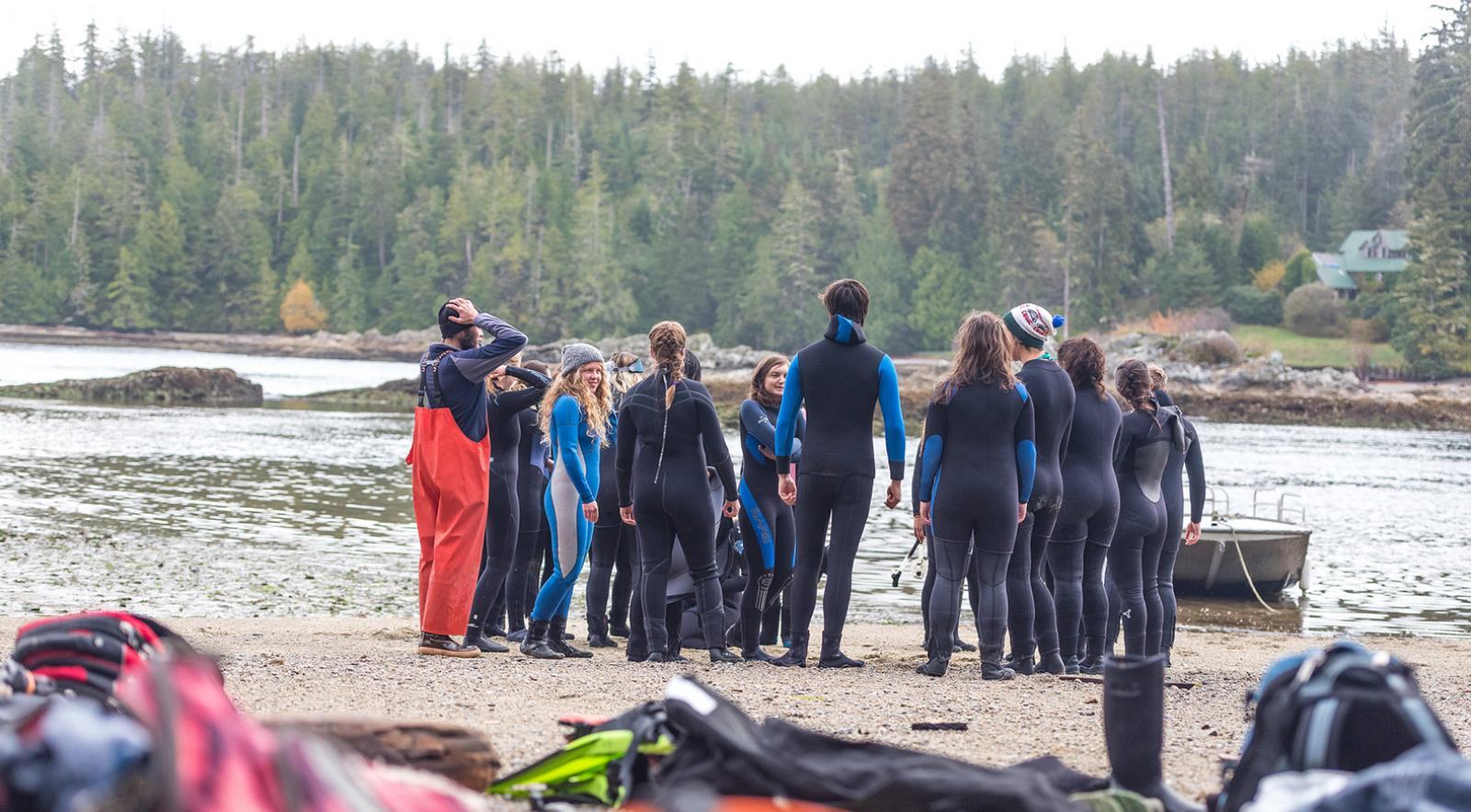 Group of students in wetsuits on shoreline by the ocean