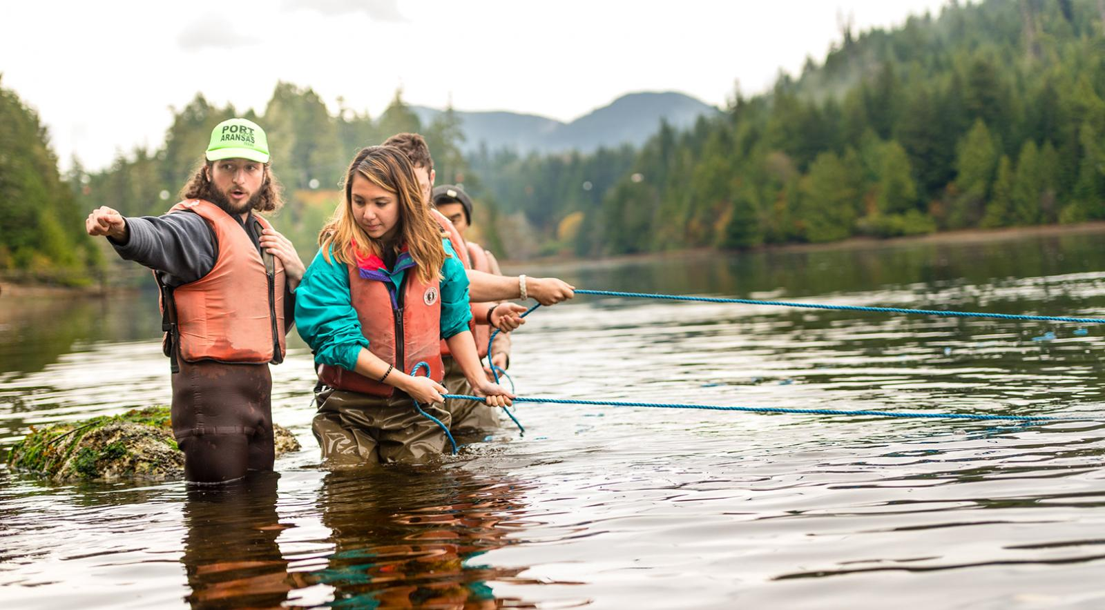Four students in waders conducting ocean research in the shore